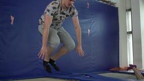De acrobaat van de beginnersmens maakt eenvoudige trucs op de trampoline stock videobeelden