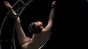 De acrobatische beweging op het roteren in de vorm van een maand voert trucs in een donkere studio uit Zwarte achtergrond Langzam stock footage