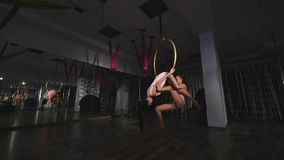 De acrobatische vrouwen hangen op luchthoepel stock videobeelden