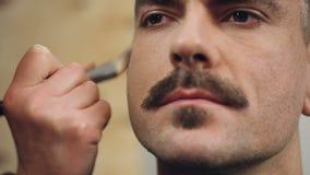 De acteur krijgt zijn make-up gedaan alvorens op reeks, make-upkunstenaar op het werk te gaan stock footage