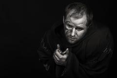 De acteur onder het mom van een monnik op een donkere achtergrond Royalty-vrije Stock Fotografie