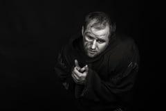 De acteur onder het mom van een monnik op een donkere achtergrond Stock Foto's