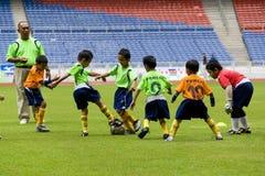 De Actie van de Voetbal van jonge geitjes Stock Foto