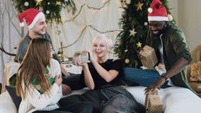 De actieve en glimlachende vrienden vangen de giften stelt vlieg in hun handen voor jonge vrouwen en mannen in de kostuums van he stock video