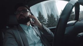 De actieve en moderne succesvolle mens zit in de auto op de bestuurders` s zetel stock footage