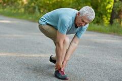 De actieve gezonde rijpe sportman bevindt zich zijdelings, voelt pijn in been na lange jogging, draagt tennisschoenen en de vrije royalty-vrije stock fotografie