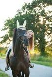 De actieve jonge vrouw berijdt een paard in aard royalty-vrije stock foto's
