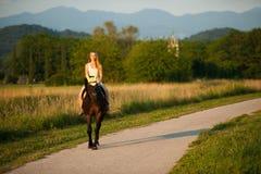 De actieve jonge vrouw berijdt een paard in aard stock fotografie