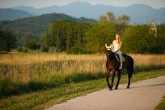 De actieve jonge vrouw berijdt een paard in aard stock foto's