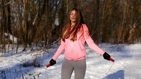 De actieve jonge vrouw voert een oefening met een touwtjespringen na een looppas uit stock videobeelden