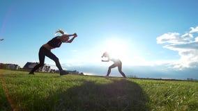 De actieve jonge vrouwen voert acrobatische stunts op het gras bij de zomerzonsondergang uit stock videobeelden