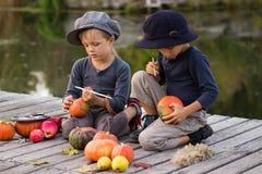 De actieve kinderen schilderen kleine Halloween-pompoenen Royalty-vrije Stock Foto's