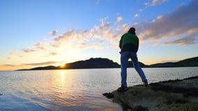 De actieve man vist op overzees van het rotsachtige de controle duwende aas van de kustvisser op de vislijn, bereidt staaf voor e stock footage