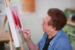 De actieve oudste schildert een beeld stock foto