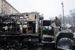 De actieve protesteerder bevindt zich op de gebrande militaire auto na strijd met politie op de straat tijdens anti-government rel Royalty-vrije Stock Afbeeldingen