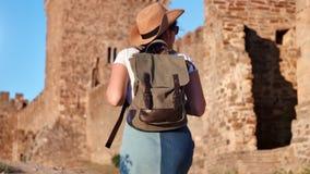 De actieve vrouw die van de Backpackertoerist op middeleeuwse kasteelmuur het bewonderen landschaps achtermening beklimmen stock videobeelden