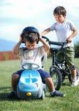 De activiteit van kinderjaren met vrachtwagenstuk speelgoed en fiets op gree Royalty-vrije Stock Foto's
