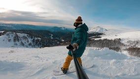 De activiteit van de de wintersport Freerider holding snowboard, overziend de vrijheid van het berglandschap stock video