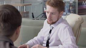 De adviseur in overhemd en band spreekt aan klant over het kopen bij autoopslag Langzame Motie stock footage