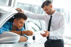 De Adviseur Showing van de autoverkoop een Nieuwe Auto aan een Potentiële Koper in S royalty-vrije stock foto