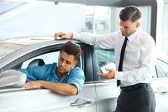 De Adviseur Showing van de autoverkoop een Nieuwe Auto aan een Potentiële Koper in S royalty-vrije stock foto's