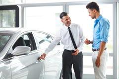 De Adviseur Showing van de autoverkoop een Nieuwe Auto aan een Potentiële Koper in S stock afbeelding