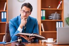 De advocaat die in het bureau werken stock afbeeldingen