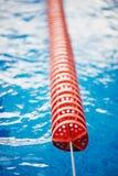 De afbakening is harde stegen in de pool Rood plastiek Zwemmers, competities, spoor Stock Foto