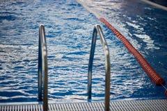 De afbakening is harde stegen in de pool Rood plastiek Zwemmers, competities, spoor Ingang aan de pool Stock Fotografie