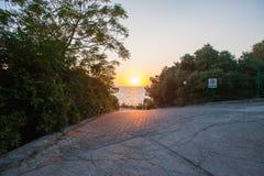 De afdaling aan het overzees bij zonsondergang, de weg aan het overzees en de zon royalty-vrije stock foto's