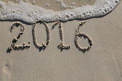 2016, de afgelopen jaartekens op het strand Stock Foto's