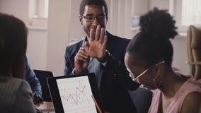 De Afrikaanse Amerikaanse bedrijfsmensenbespreking, toont gebaren en communiceert op bureauvergadering, die laptop diagrammen bek
