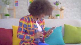 De Afrikaanse Amerikaanse die vrouw met een afrokapsel gebruikt een smartphone en over de winst komt weten stock videobeelden
