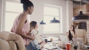 De Afrikaanse Amerikaanse gelukkige vrouwelijke leider spreekt aan collega's, gangen uit het bureau Multi-etnische groep in moder stock videobeelden