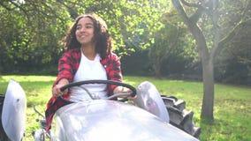 De Afrikaanse Amerikaanse gemengde jonge vrouw die van de rastiener een grijze tractor drijven door een zonnige appelboomgaard stock videobeelden
