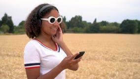 De Afrikaanse Amerikaanse jonge vrouw die van de meisjestiener het witte zonnebril lopen die aan muziek op draadloze hoofdtelefoo stock footage