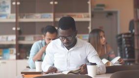 De Afrikaanse Amerikaanse mannelijke universiteit studen het voorbereidingen treffen voor examens in de bibliotheek stock videobeelden