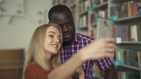 De Afrikaanse Amerikaanse mens en de Europese dame nemen selfie in de bibliotheek stock video