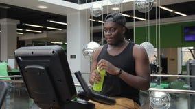 De Afrikaanse Amerikaanse praktijken op een hometrainer en drinkt water van fles stock video