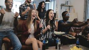 De Afrikaanse Amerikaanse sportenfans vieren thuis winst De hartstochtelijke verdedigers schreeuwen het letten op spel op TV 4k l royalty-vrije stock afbeeldingen