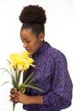 De Afrikaanse Amerikaanse vrouw glimlacht terwijl het ruiken van verse bloemen Stock Foto