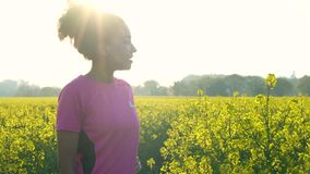 De Afrikaanse Amerikaanse vrouwelijke jonge vrouw die van de meisjestiener of en een fles water op gebied van gele bloemen in wer stock videobeelden