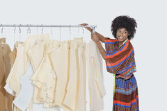 De Afrikaanse Amerikaanse vrouwelijke ontwerper met het naaien van patronen op kleren rekt over grijze achtergrond Stock Fotografie