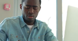De Afrikaanse Amerikaanse zakenman schrijft nota's bekijkend laptop monitor die in bureau werken stock footage
