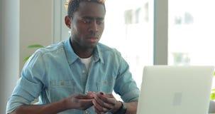 De Afrikaanse Amerikaanse zakenman schrijft nota's bekijkend laptop monitor die in bureau werken stock video