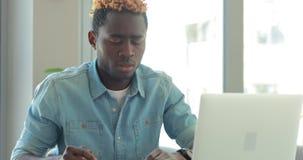 De Afrikaanse Amerikaanse zakenman schrijft nota's bekijkend laptop monitor die in bureau werken stock videobeelden