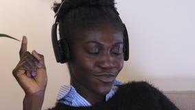 De Afrikaanse dame luistert thuis muziekdans stock footage