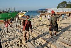De Afrikaanse dokwerkers maken Timmerhoutboot in haven van Zanzibar leeg stock afbeelding