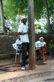 De Afrikaanse jonge mens kleedde zich in wit, die zich op de rand van bevinden Royalty-vrije Stock Foto