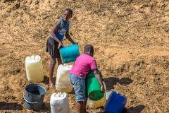 De Afrikaanse kinderen verzamelen water Royalty-vrije Stock Afbeeldingen